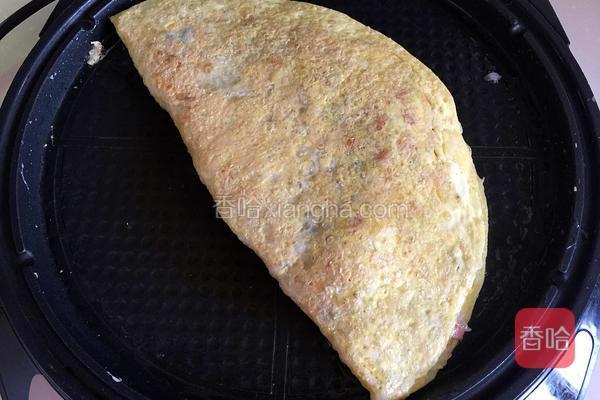 另一半蛋饼盖在炒饭上,蛋饼煎至金黄盛出。